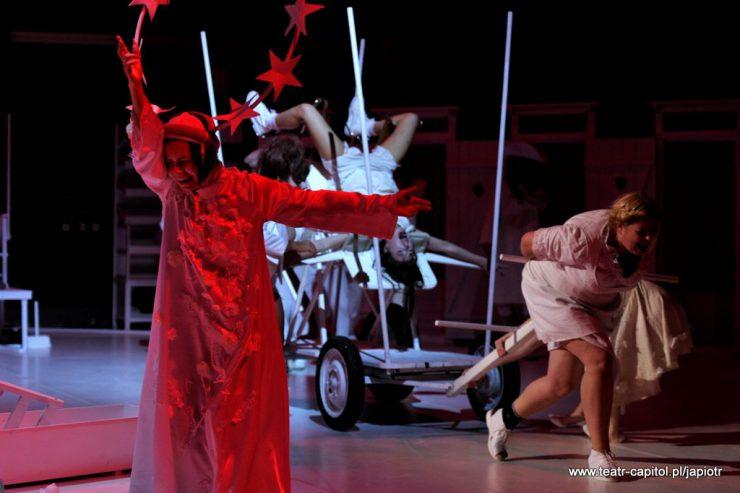 Z lewej strony oświetlona czerwono postać stojącej kobiety. Amien jedną rękę ma uniesioną do góry, drugą skierowaną w bok. W tle kobieta ciągnie wózek, na którym znajduje się krzycząca kobieta, leżąca do góry nogami.