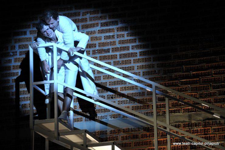 Dwaj ubrani na biało mężczyźni na szczycie schodów. Piotr Rivière przytrzymuje się o poręcz, Młynarz jest na jego plecach, zwisa bezwładnie.