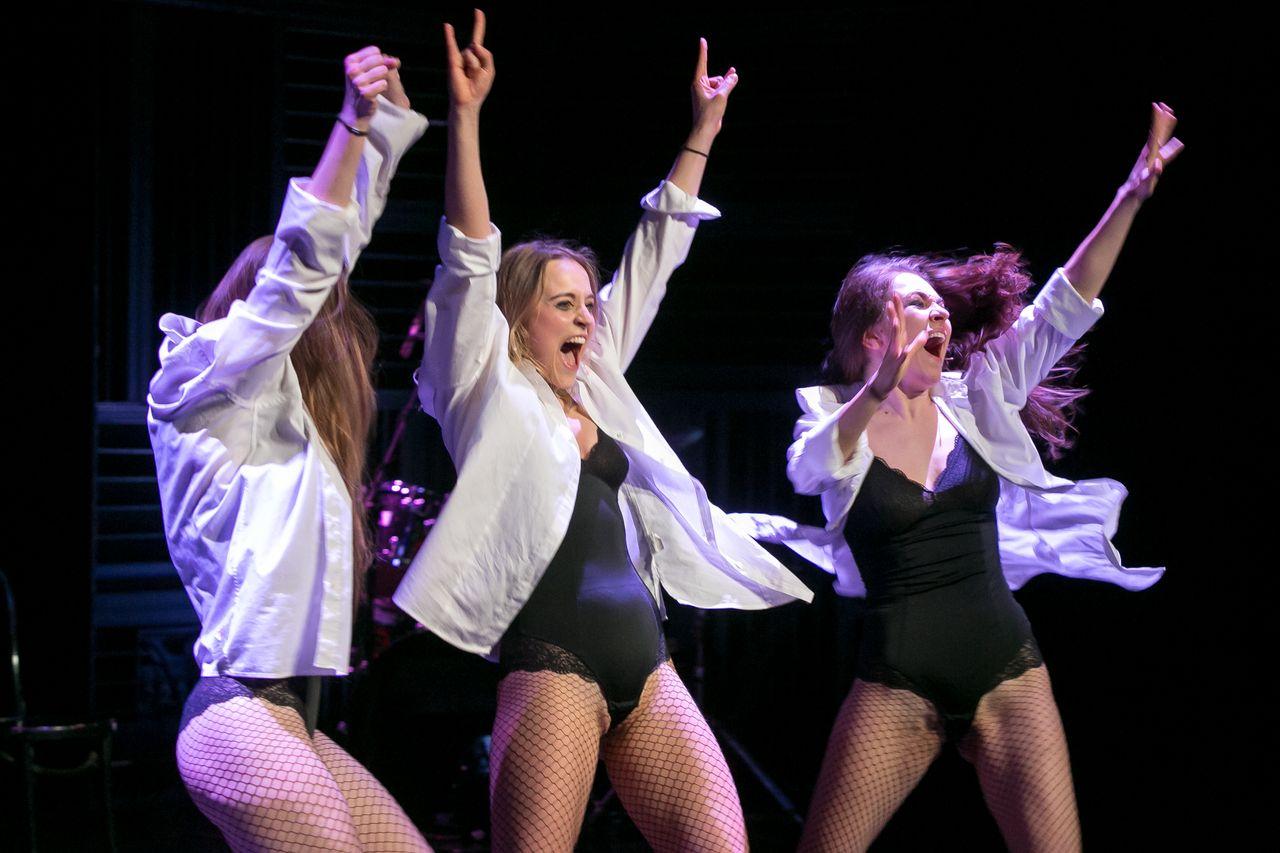 Na ciemnym tle trzy młode kobiety w ekspresyjnym tańcu, z rękami wzniesionymi w górze. Wołają coś lub śpiewają. Mają na sobie czarne, elastyczne body wykończone koronką, siatkowe rajstopy-kabaretki i białe, rozpięte koszule.