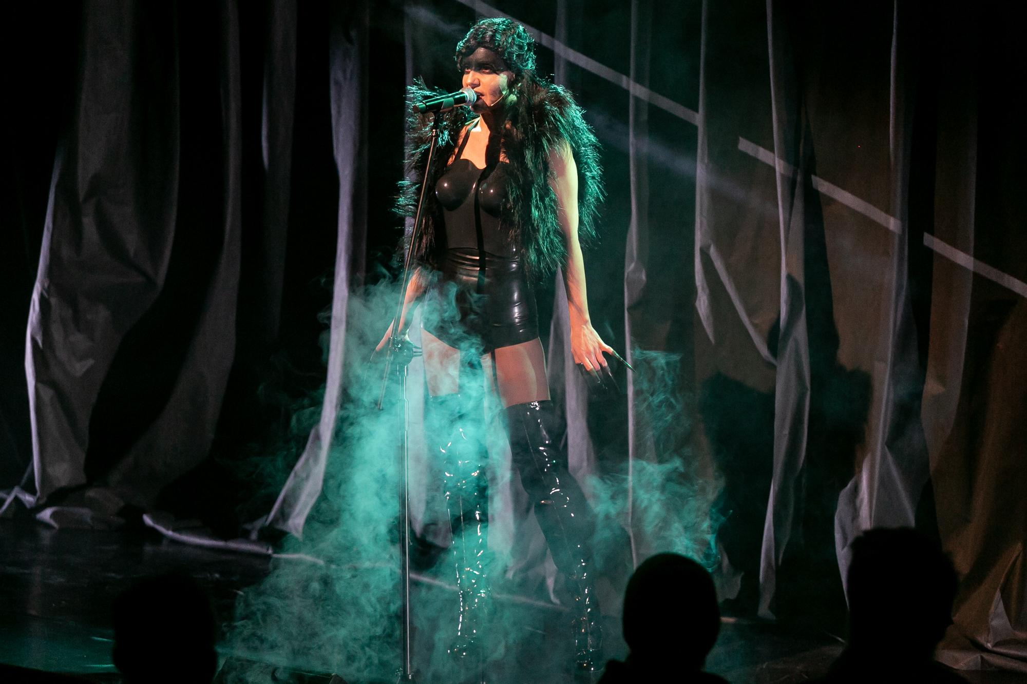 W centrum kadru, na tle czarnej, fałdowanej kurtyny, stoi Norbert Zły (Lilith), kobieta-drag queen. Ma czarne, krótkie włosy ułożone w falowaną fryzurę, czoło i powieki pomalowane czarną farbą. Jest w czarym lateksowym kostiumie bez ramion i rękawów, z krótkimi spodenkami. Ma lateksowe kozaki za kolano i czarne, przejrzyste rajstopy, pace zakończone nakładanymi, czarnymi szponami, na ramionach krótkie, czarne, puszyste futerko bez rękawów. Śpiewa do mikrofonu, do kolan przesłania ją dym. Scena jest oświetlona seledynowym światłem.