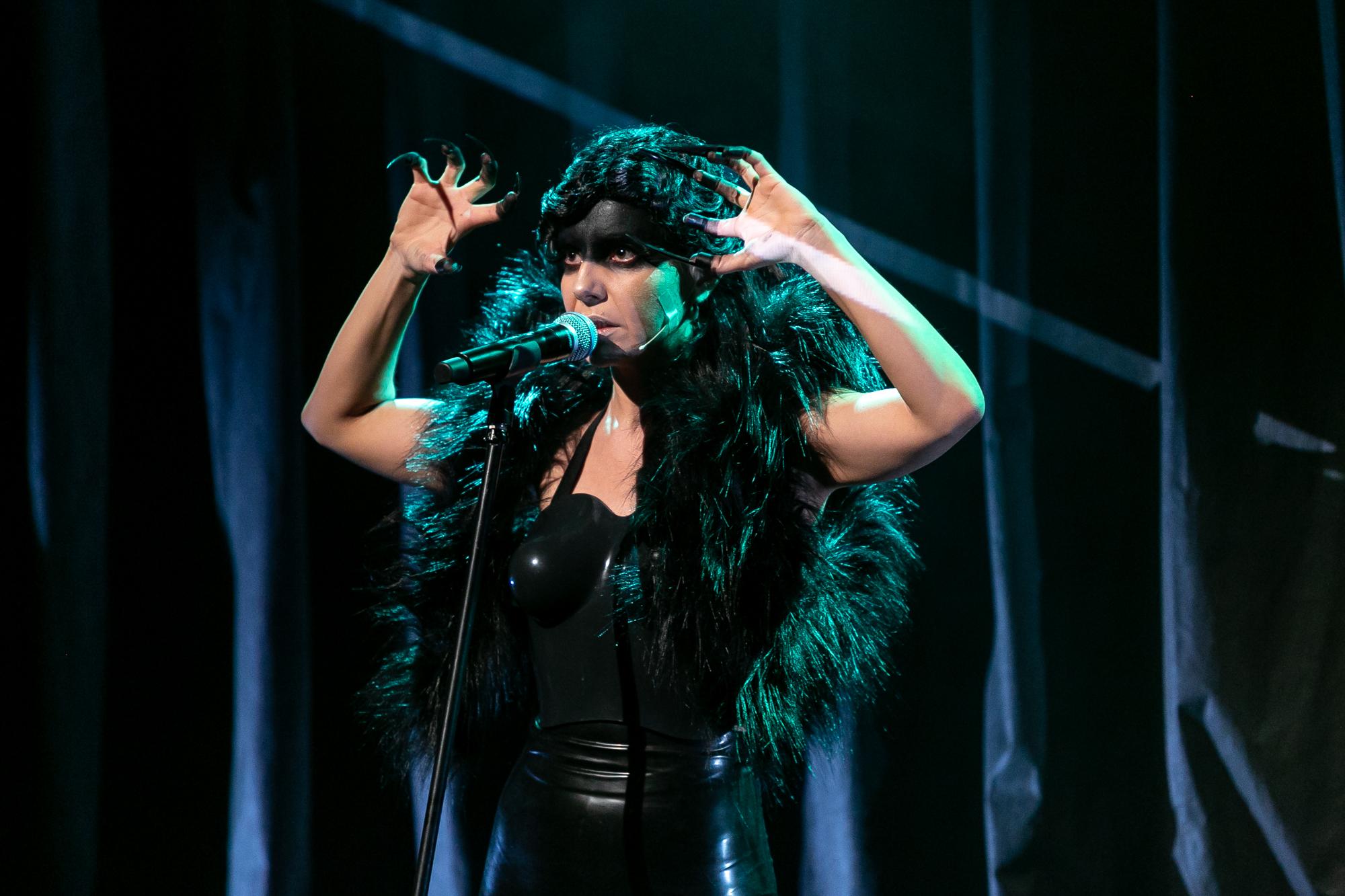 W centrum kadru, na tle czarnej, fałdowanej kurtyny, stoi Norbert Zły (Lilith) -kobieta-drag queen. Widać ją do bioder. Ma czarne, krótkie włosy ułożone w falowaną fryzurę, czoło i powieki pomalowane czarną farbą. Jest w czarym lateksowym kostiumie bez ramion i rękawów. Śpiewa do mikrofonu, wznosząc ręce na wysokość czoła, ma palce zakończone nakładanymi, czarnymi szponami, na ramionach krótkie, czarne, puszyste futerko bez rękawów. Scena jest oświetlona seledynowym światłem.