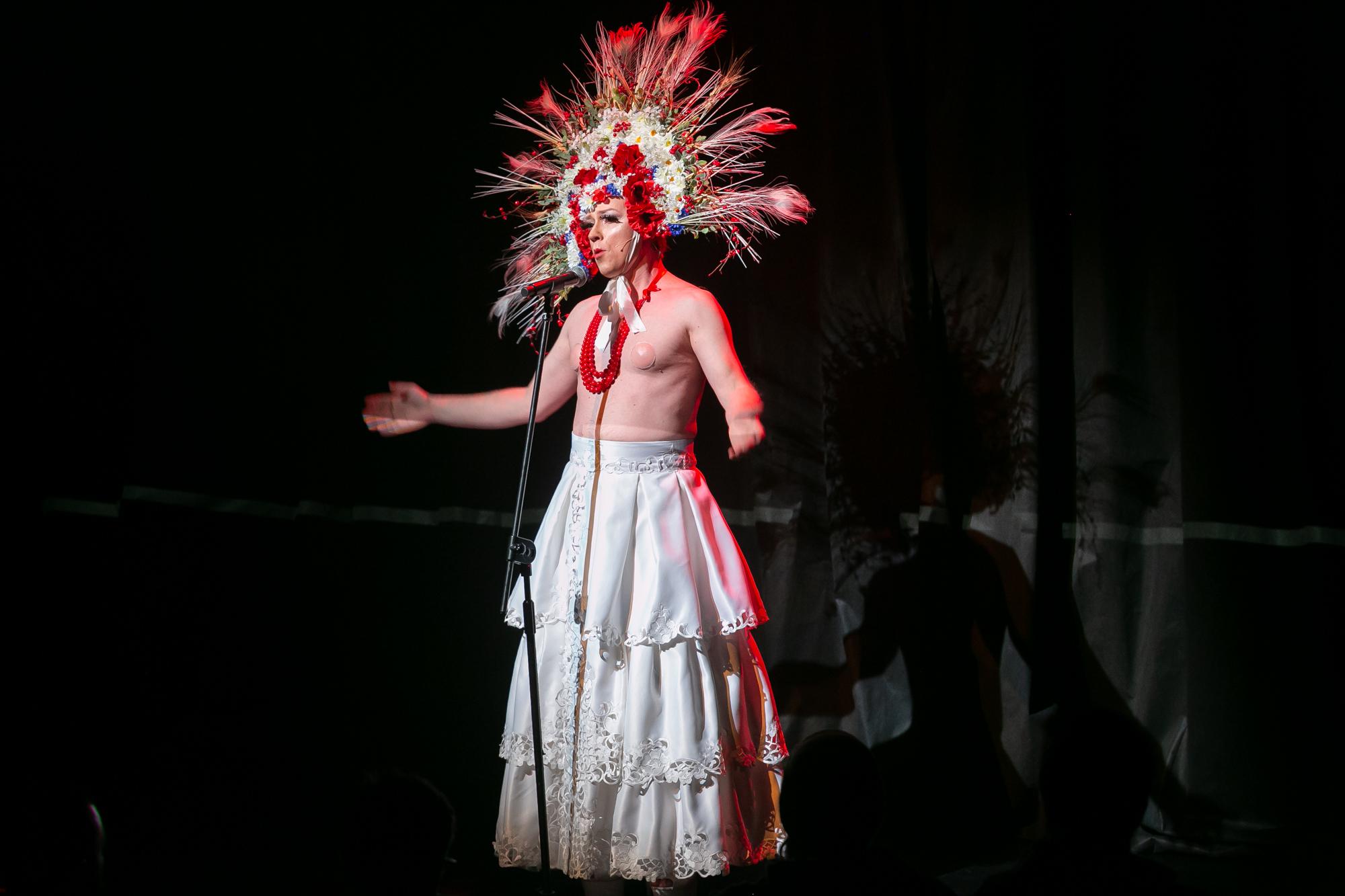 Na tle czarnej, fałdowanej kurtyny stoi przed mikrofonem Karol Polski (Karolina) - ężczyzna-drag queen. Na głowie ma ogromny wieniec z kłosów zbóż, pawich piór, sztucznych maków, chabrów, rumianku i jarzębiny, mocny makijaż z długimi sztucznymi rzęsami, na szyi kilka sznurów czerwonych korali. Jest nagi do pasa, ma długą białą, płócienną spódnicę z trzech falban, wykończonych ażurowym haftem. Rozkłada ręce.
