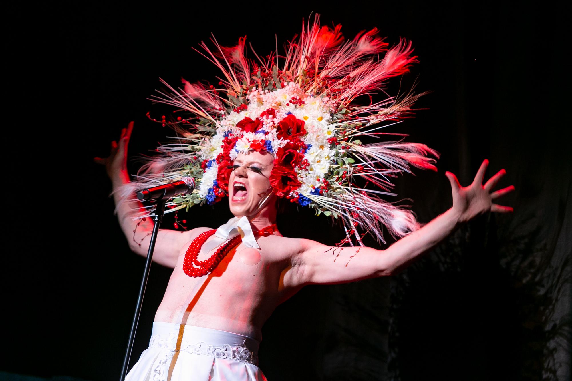 Na tle czarnej, fałdowanej kurtyny stoi przed mikrofonem Karol Polski (Karolina) - mężczyzna-drag queen. Na głowie ma ogromny wieniec z kłosów zbóż, pawich piór, sztucznych maków, chabrów, rumianku i jarzębiny, mocny makijaż z długimi sztucznymi rzęsami, na szyi kilka sznurów czerwonych korali. Jest nagi do pasa. Wznosi szeroko rozłożone ręce na wysokość głowy.