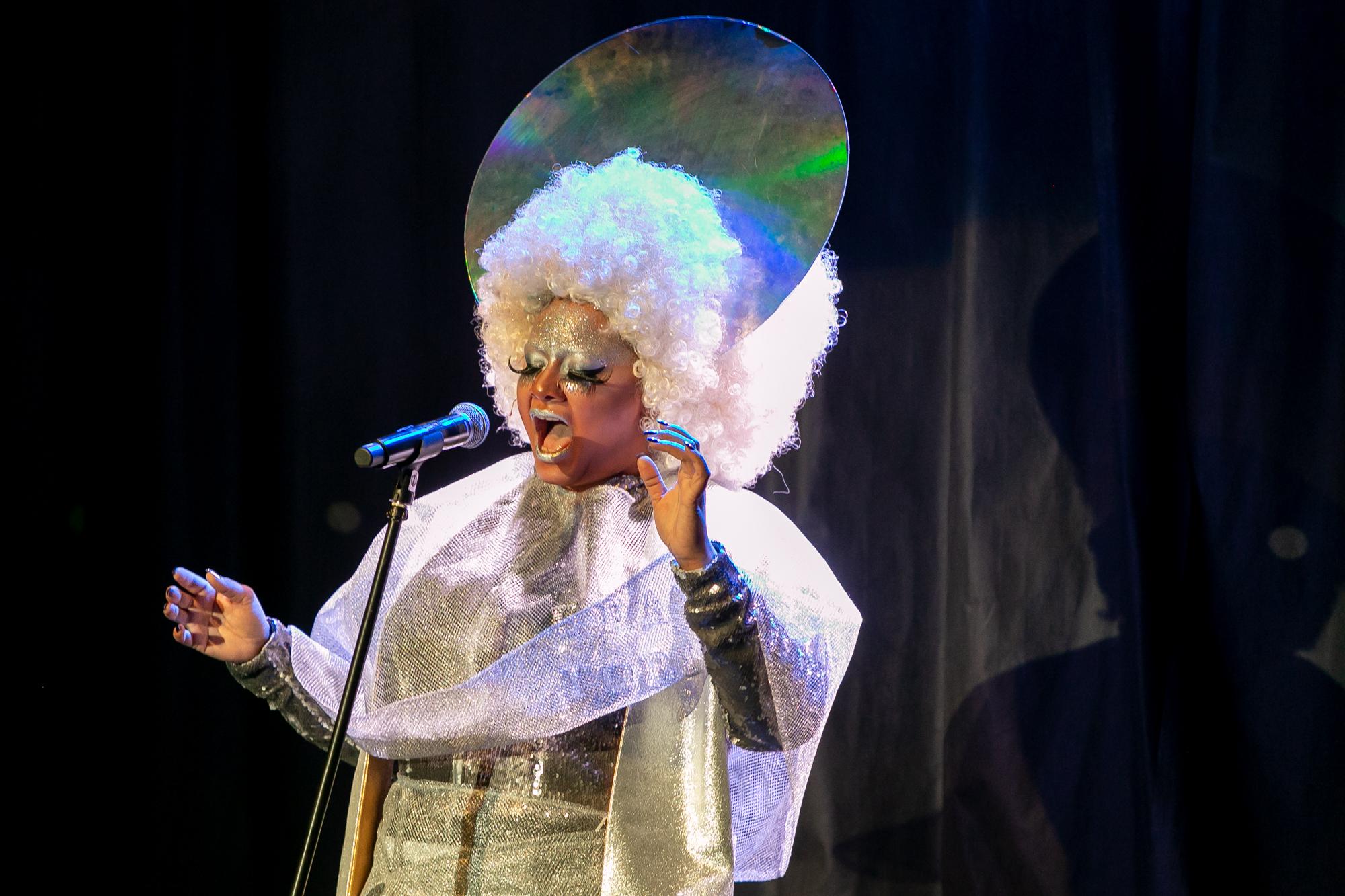 W centrum kadru śpiewa do mikrofonu Przemek Boski (Juro-diva) -kobieta-drag queen.