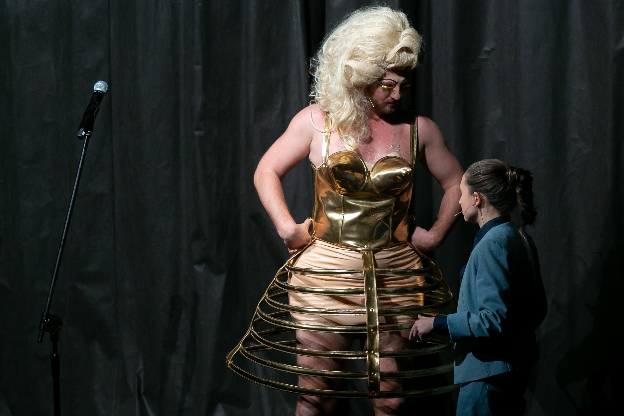 Piotr Piękny (Ariana Konsza) - wysoki mężczyzna-drag queen w blod peruce, złotym gorsecie i stelażu rozkloszowanej spódnicy trzyma się pod boki i rozmawia z Konradem Konradem - drobną kobietą w popielatym męskim garniturze. Oboje stoją na tle czarnej, pofałdowanej kurtyny.