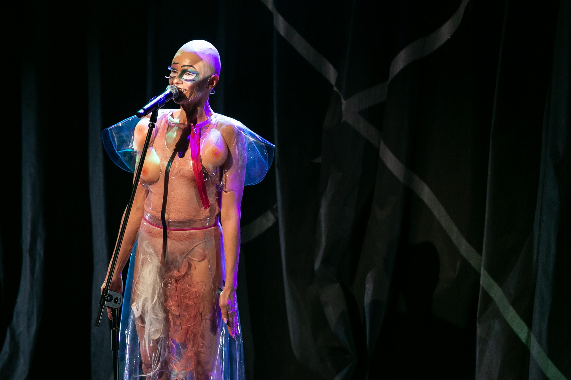 Na tle czarnej, pofałdowanej kurtyny stoi Damian Alien (D'alien) -kobieta-drag queen w lateksowym, nagim kostiumie z męskim owłosieniem torsu i trzema sztucznymi piersiami, rozmieszczonymi niesymetrycznie na torsie. W miejscu włosów łonowych do kostiumu przyczepiona jest długa kolorowa, falująca peruka. Postać okryta jest przezroczystą, plastikową narzutką z krótkimi rękawami, ma na głowie łyskę (perukę-łysinę).