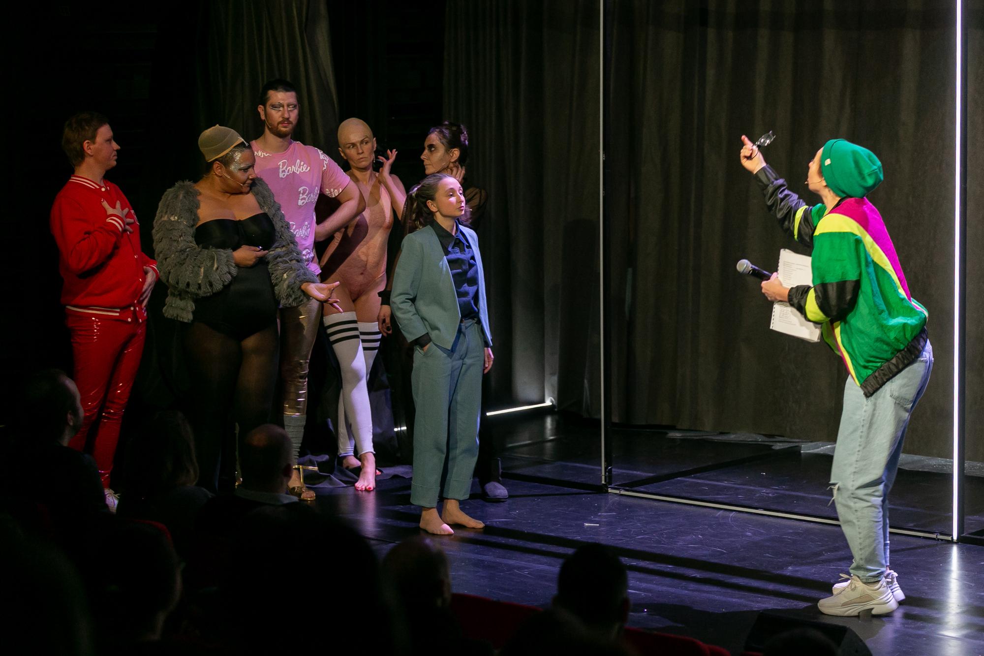 Na tle częściowo odsłoniętej czarnej kurtyny i stelażu z pionowych i poziomych świetlówek po lewej stronie stoi grupka drag queens i Konrad Konrad. Ze sceptycznymi minami słuchają Reżysera, który stoi po prawej stronie sceny z tekstem sztuki i mikrofonem w lewej ręce, wymachuje prawą ręką i coś im emocjonalnie tłumaczy.