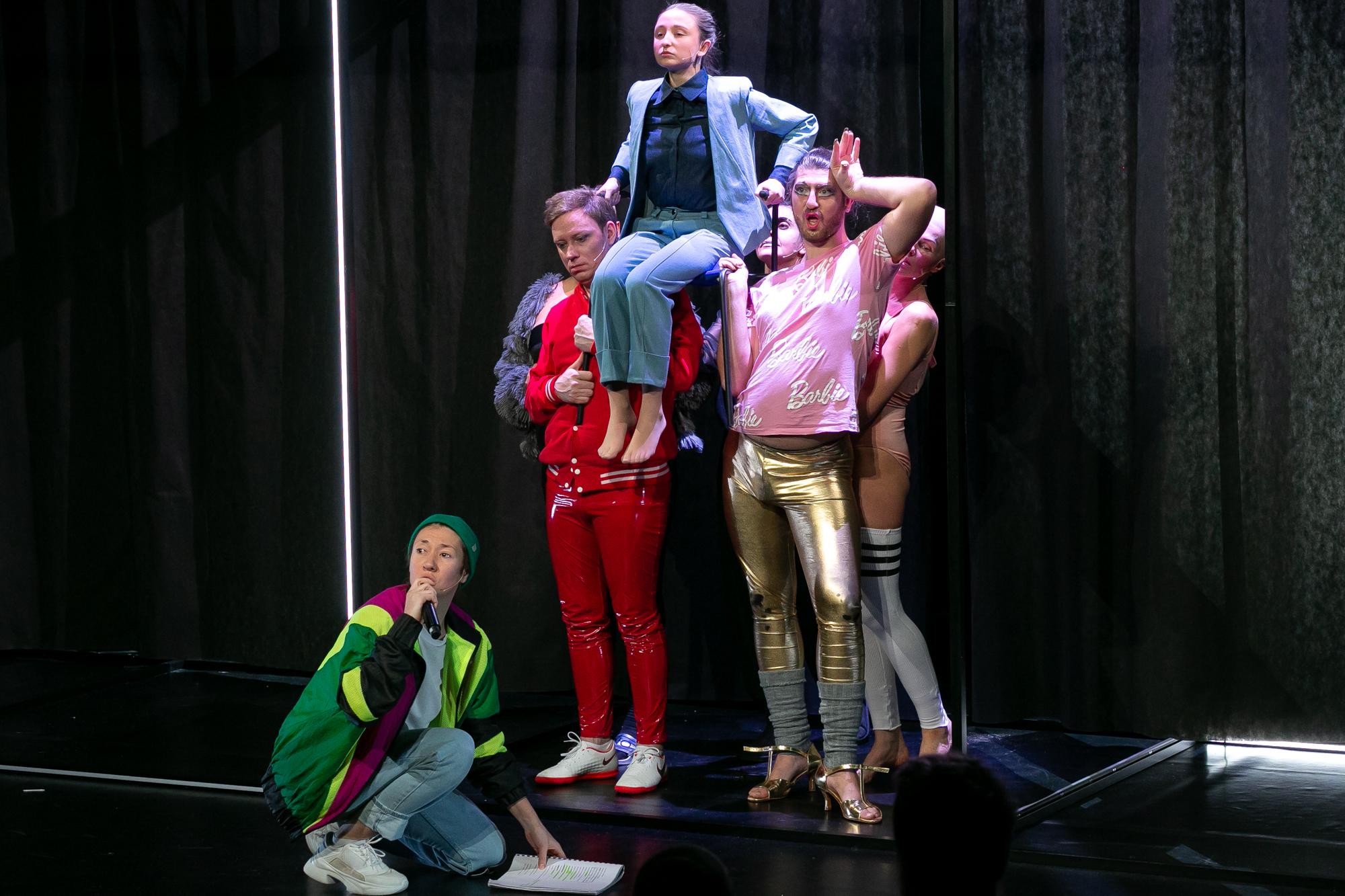 Na tle czarnej kurtyny, obok pionowej, jaskrawej świetlówki, stoi grupa drag queens, trzymając na ramionach siedzacego Konrada Konrada. U ich stó siedzi na podłodze Reżyser - kobieta w zielonej czapce z dzianiny, kolorowej bluzie, dżinsach i białych adidasach, trzymająca tekst sztuki.