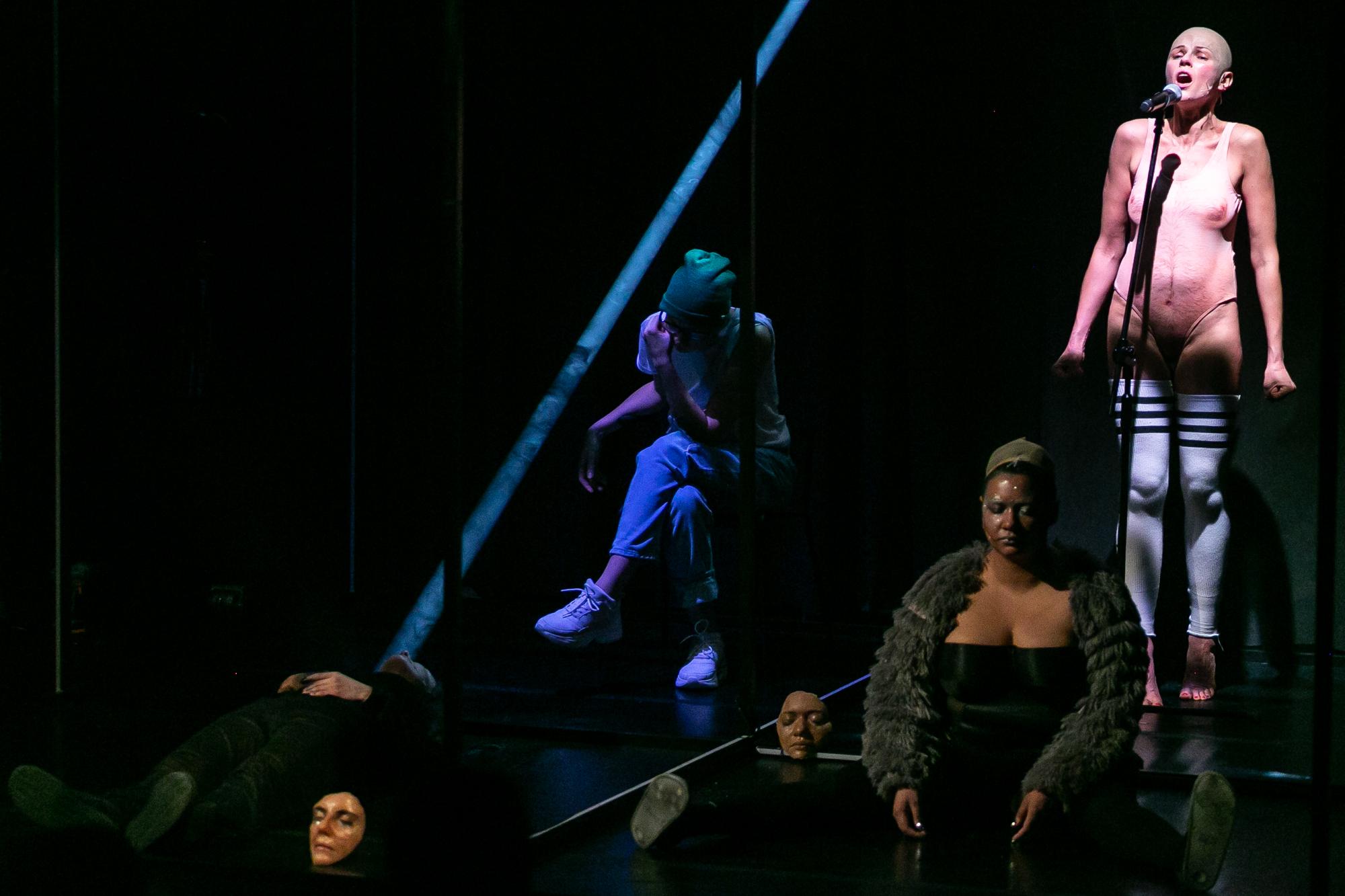 Scenę w ciemnościach przecina ukośny, wąski promień błękitnego światła. Po lewej leży na podłodze ciemno ubrana postać o niewidocznej twarzy, leżą dwie maski przedstawiające twarze drag queens. W centrum siedzi Reżyser, opiera pochylone czoło na lewej ręce, założył nogę na nogę. Po prawej siedzi Przemek Boski (Juro-diva), kobieta drag queen bez makijażu, w futrzanj narzutce na ramionach i siatce na włosach. Za nią stoi Damian Alien (D'alien) - kobieta drag queeen w lateksowym nagim kostiumie i białych getrach do połowy uda,, bez ozdób i charakteryzacji.