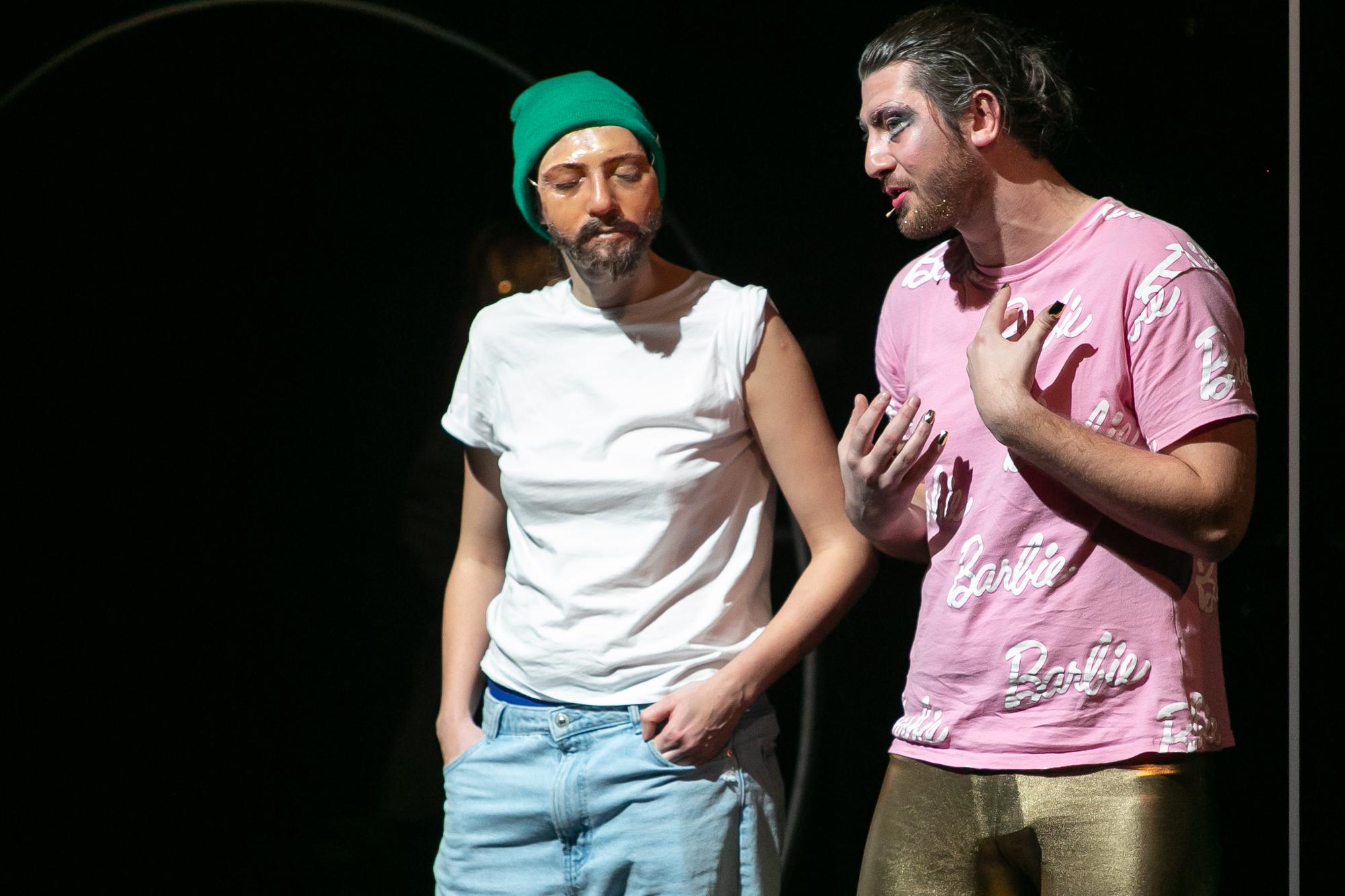 """Na ciemnej scenie dwie postaci w ujęciu do bioder. Po lewej stronie Reżyser- kobieta w białej koszulce z krótkim rękawem i dżinsach, w zielonej czapce z dzianiny. Na twarzy ma maskę Piotra Pięknego. Słucha, co mówi do niej gestykulujący, stojący po prawej stronie Piotr Piękny - mężczyzna w makijażu, różowej koszulce z białymi napisami """"Barbie"""" i w złotych legginsach."""