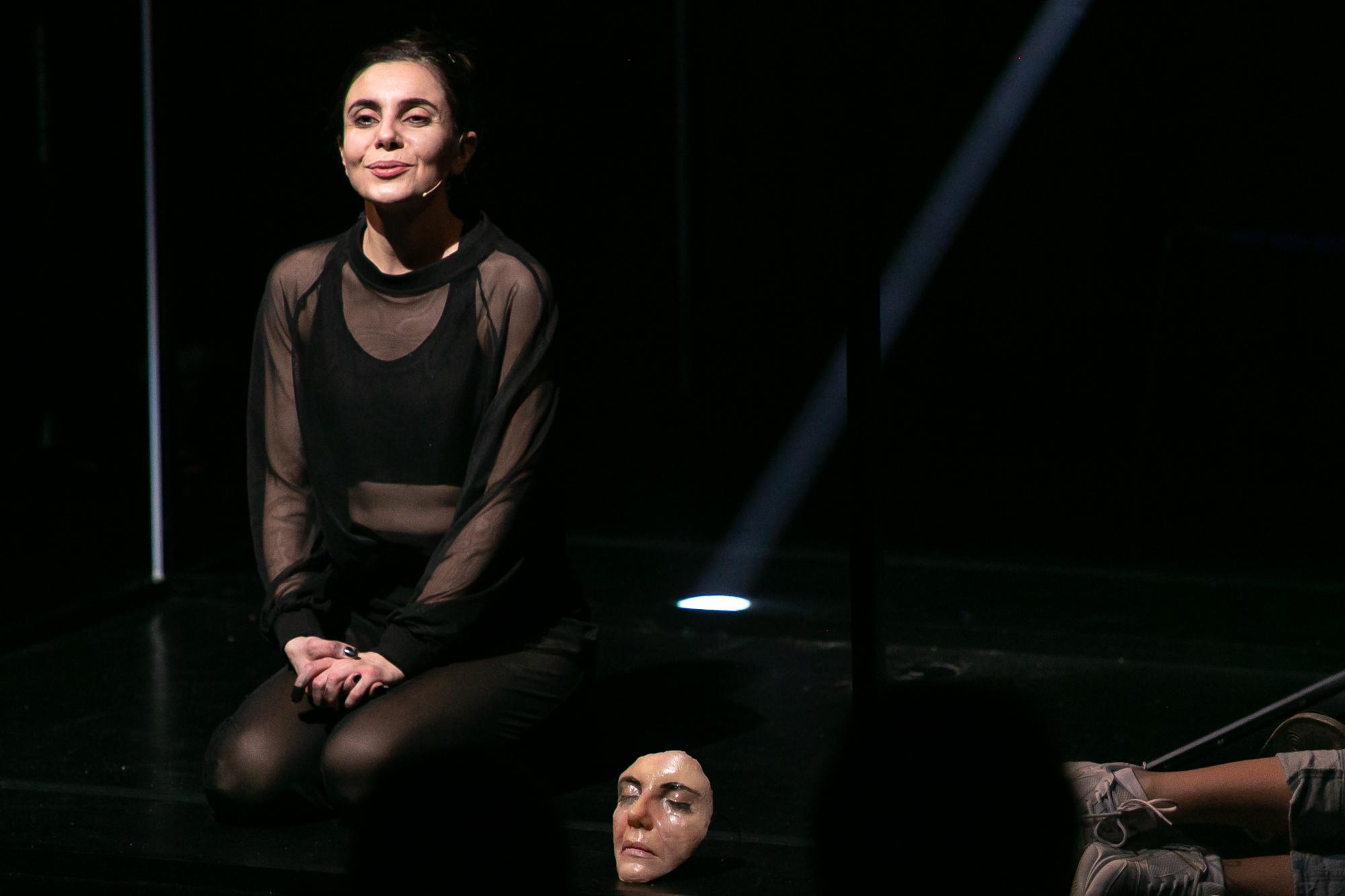 Na ciemnej scenie siedzi Norbert Zły - kobieta w ciemnym stroju, bez makijażu. Obok niej leży na podłodze maska, przedstawiająca jej twarz.