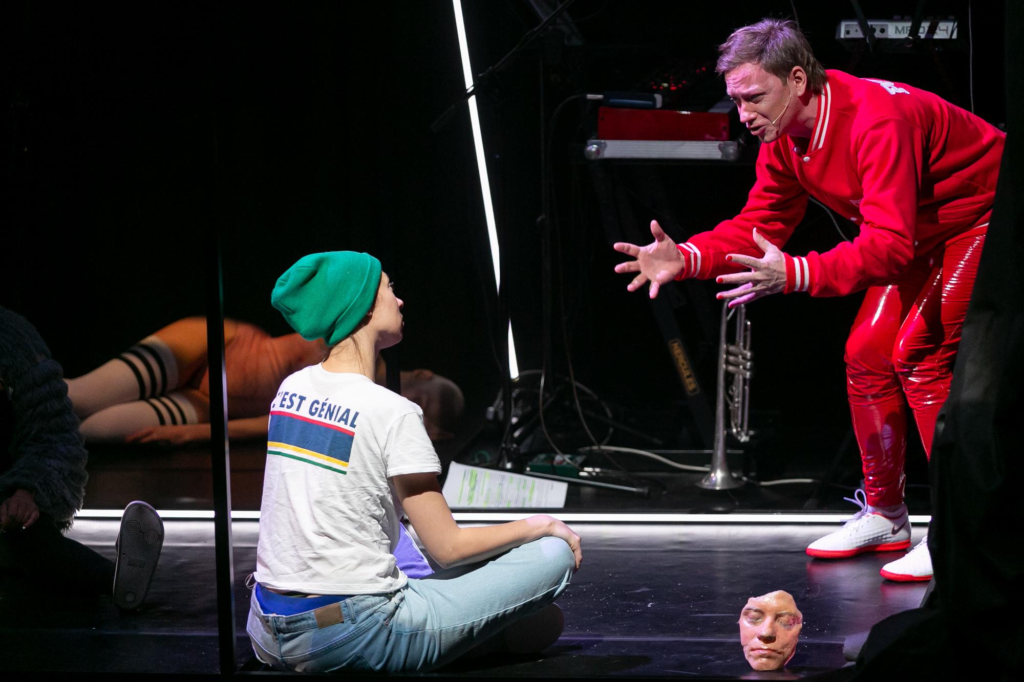"""Na pierwszym planie, odwrócony do publiczności prawym półprofilem, siedzi po turecku Reżyser - kobieta w białej koszulce z napisem na plecach """"C'EST GENIAL"""", w zielonej czapce z dzianiny i w dżinsach, spod ktorych wystają niebieskie majtki. Słucha, co mówi pochylony nad nią Karol Polski - gestykulujący w emocjach mężczyzna w czerwonym dresie z białymi wstawkami, w biało-czerwonych butach sportowych, z paznokciami pomalowanymi na czerwono. Obok nich na podłodze leży maska - odlew twarzy Karola Polskiego."""