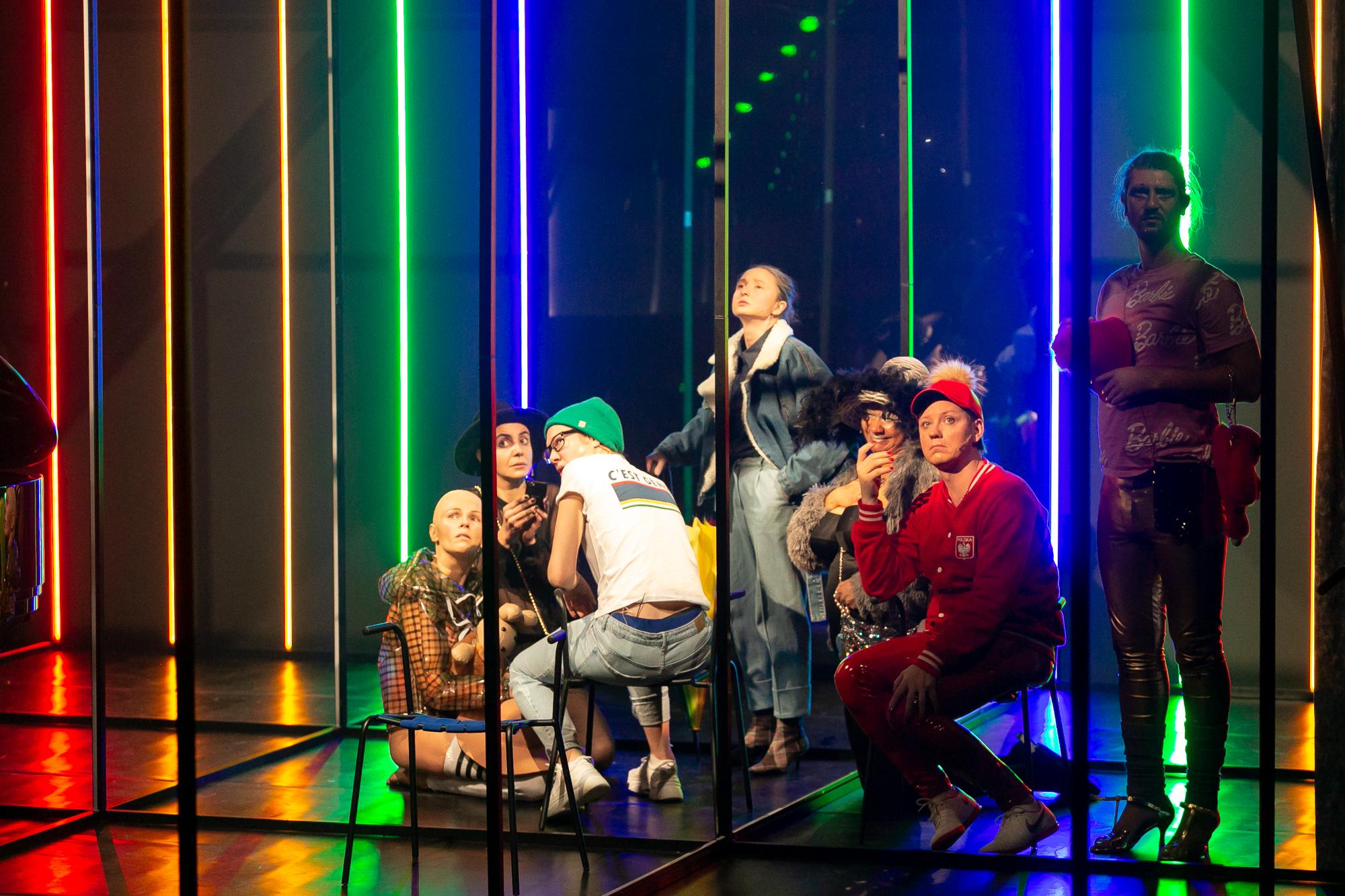 W centrum sceny, wewnątrz metalowego stelaża, siedzi grupa drag queens w prywatnych strojach. Wśród nich jest Reżyser i Konrad Konrad. Po prawej stroni stoi Piotr Piękny. Scena oświetlona jest świetlówkami w kolorach tęczy.