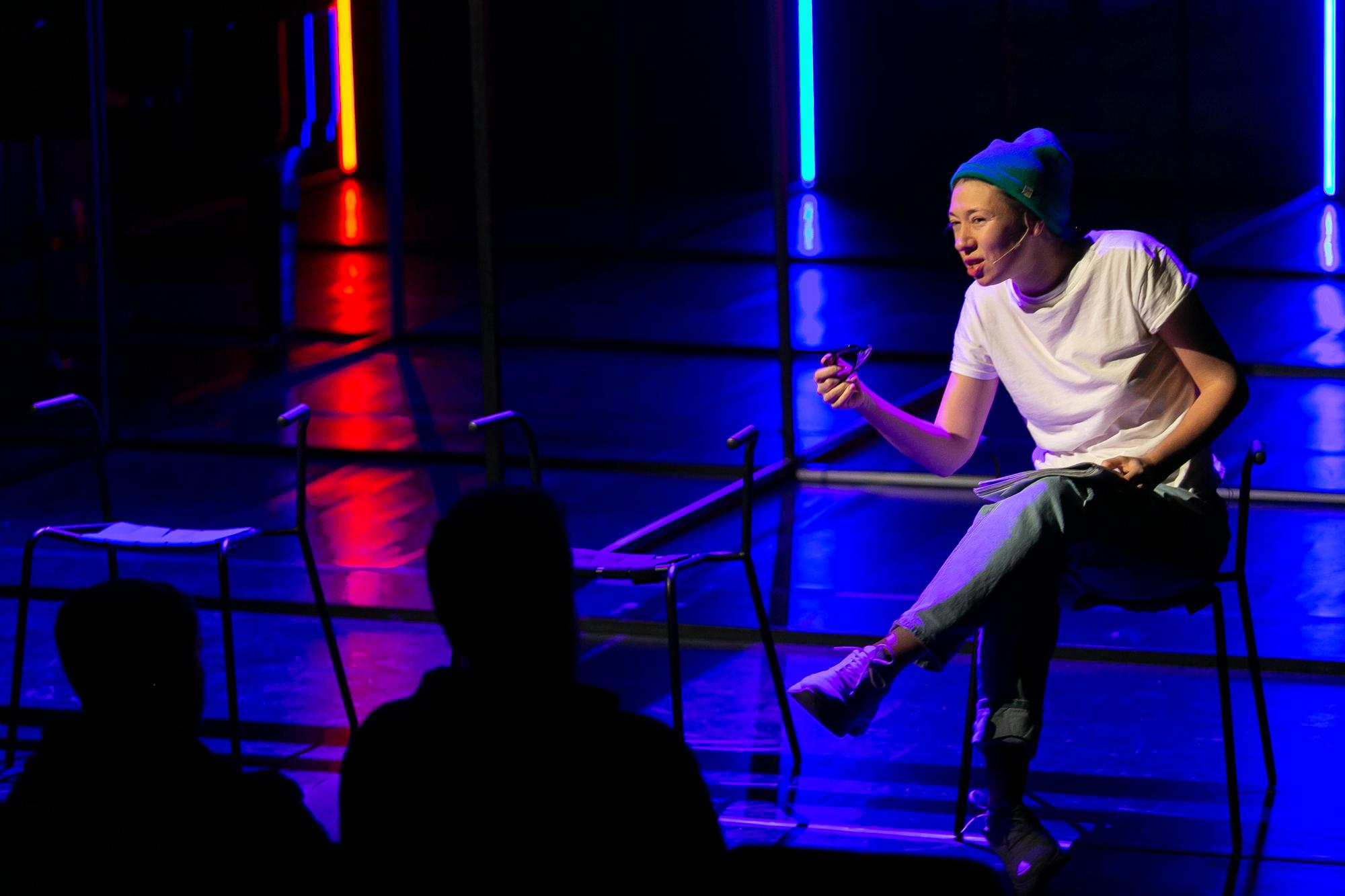 Na przedzie sceny, oświetlonej błękitnym światłem z pomarańczowym kontrapunktem polewej stronie stoją trzy metalowe krzesła bez oparcia. Na krześle z prawej strony siedzi Reżyser - kobieta w białej koszulce, czapce z dzianiny i dżinsach. Mówi coś do publiczności, gestykulująć ręką, w której trzyma okulary.