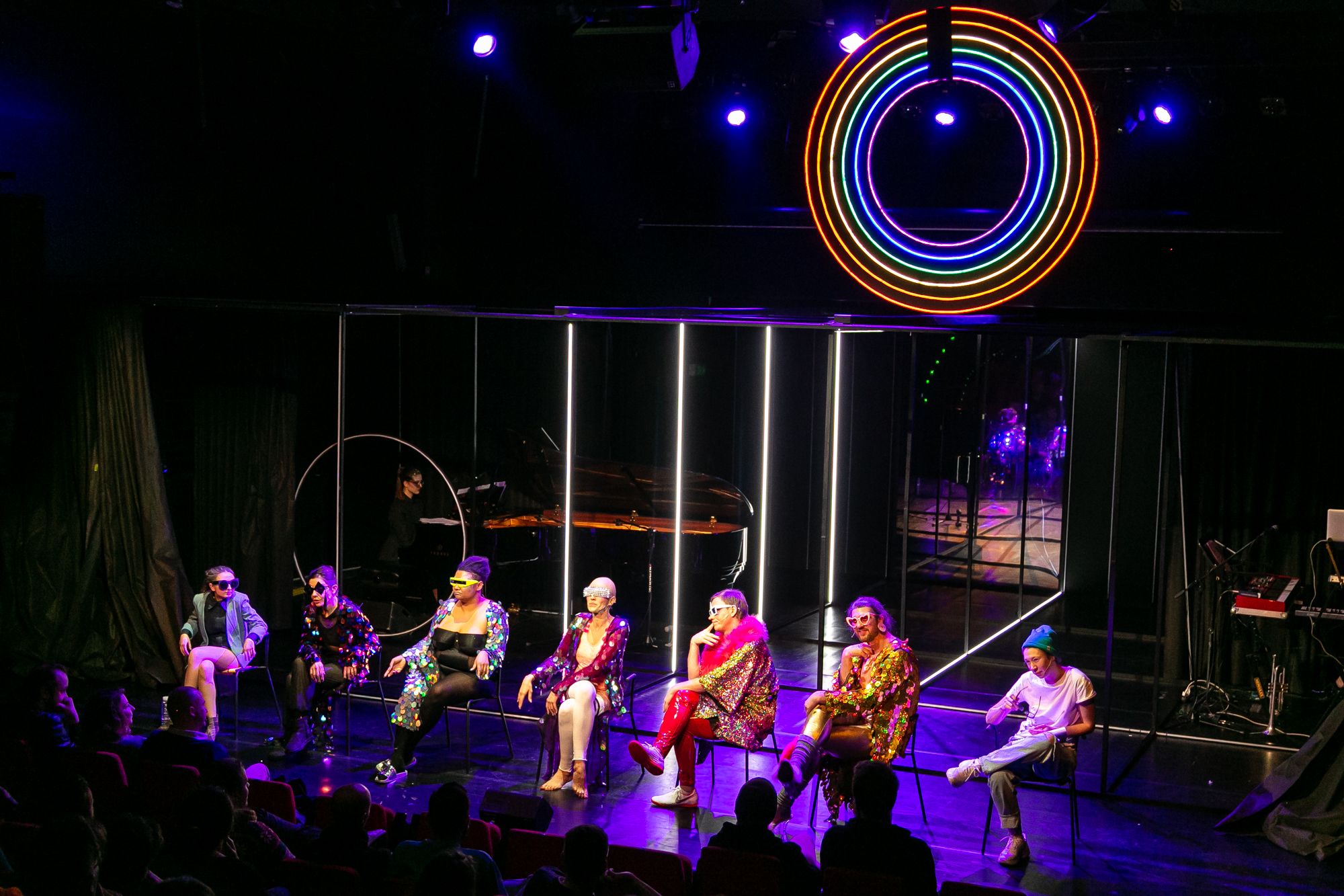 Na przedzie sceny siedzą na krzesłach drag queens, Konrad Konrad i Reżyser. Kurtyna jest odsłonięta, widać metalowy stelaż z pionowymi świetlówkami, nad sceną wisi neonowe koło w kolorach tęczy.