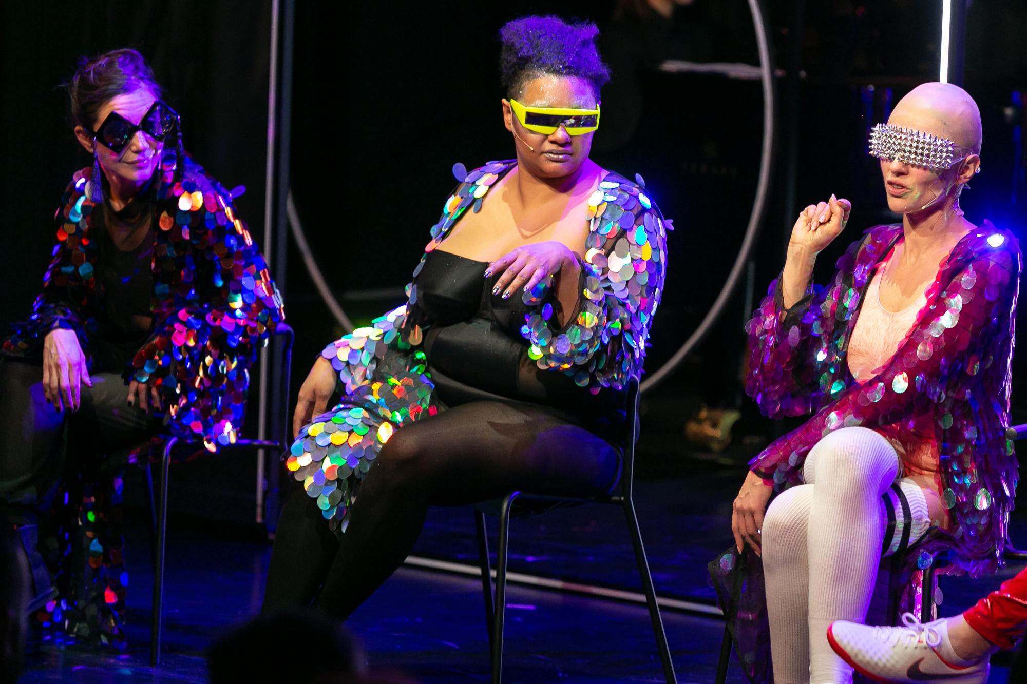 Na ciemnej scenie siedzą na krzesłach trzy drag queens. Norbert Zły w kwadratowych okularach z ozdobnymi chwostami i plaszczu z kolorowych, wielkich cekinów; Przemek Boski w czarnym kombinezonie z lycry i narzutce z kolorowych cekinów, w wąskich, czarno-żółtych okularach, i Damian Alien w prostokatnych okukarach ze srebrnych ćwieków, białych getrach i bordowej narzutce z cekinów