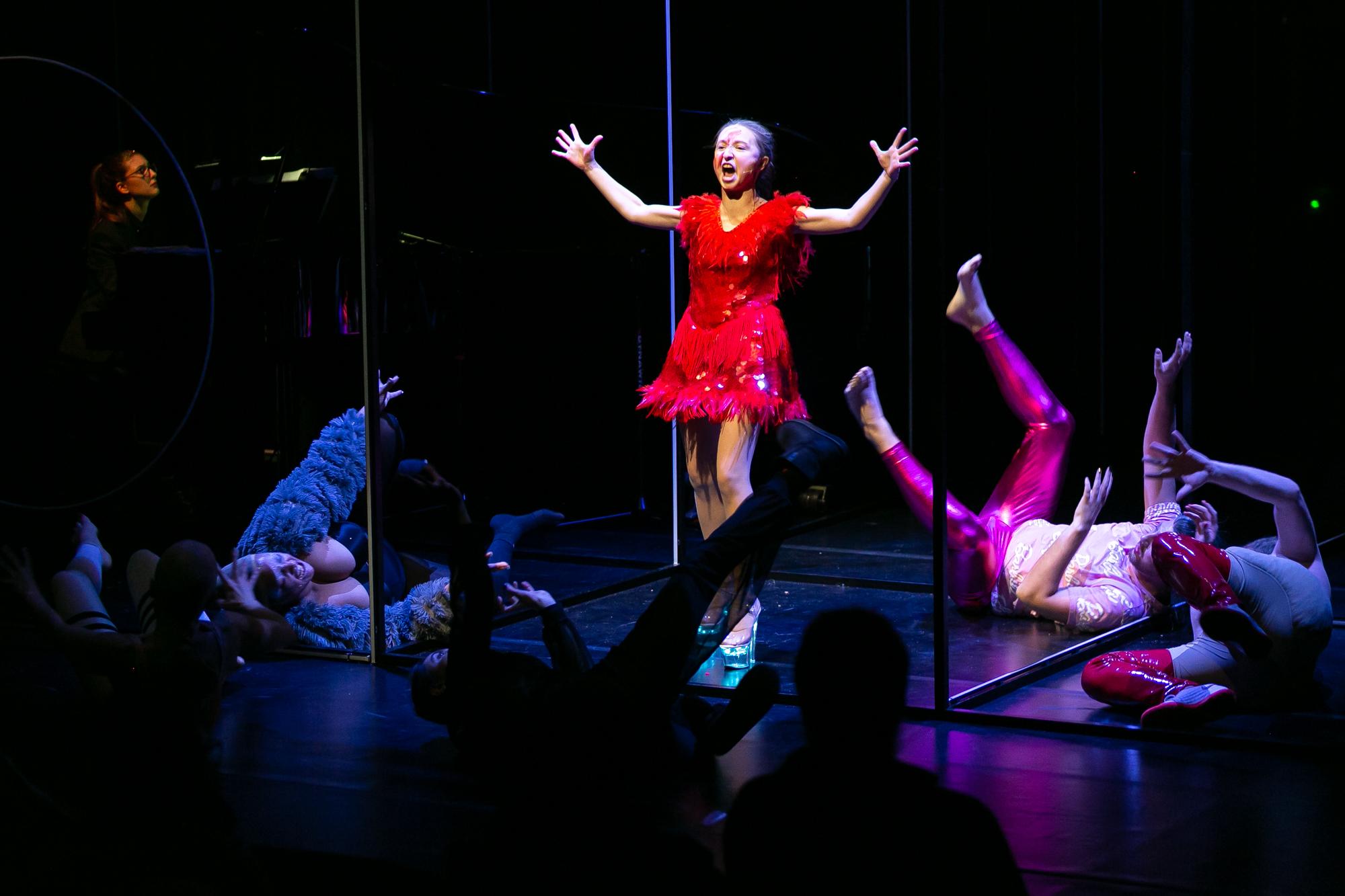 Pośrodku sceny Konrad Konrad - kobieta w krótkiej, czerwonej sukience z frędzlami i w srebrnych butach na platformie ekspresyjnie coś śpiewa lub krzyczy z rękami wzniesionymi w górę. Wokół niej tarzają się po podłodze cztery postaci drag queens.