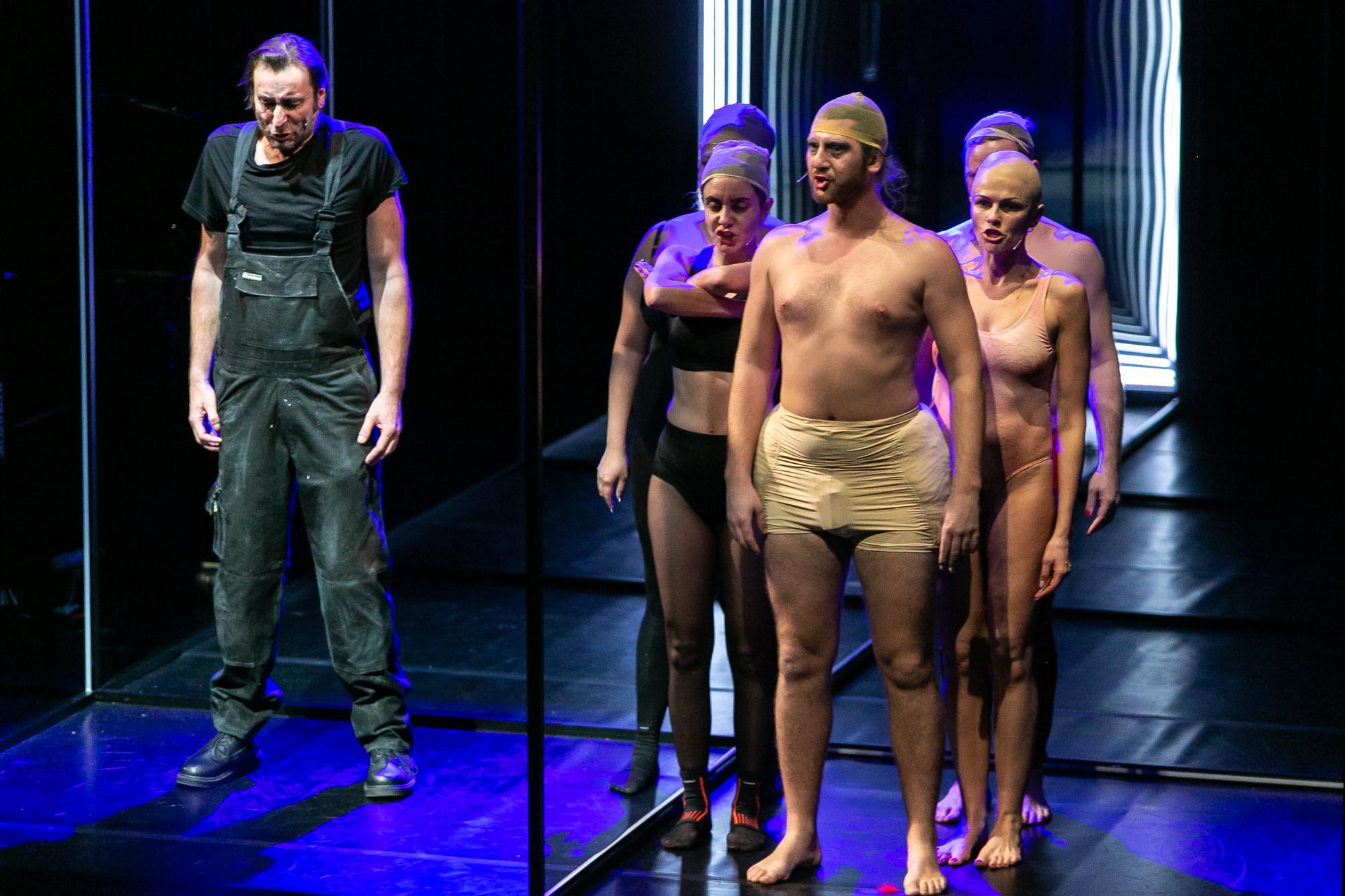 Na scenie oświetlonej błękitnym światłem po lewej stronie stoi Techniczny - wysoki mężczyzna w roboczym stroju, po prawej - grupk drag queens w bieliźnie i siatkach na włosy. Z przodu grupy Piotr Piękny - mężczyzna ubrany w cieliste, duże majtki z poduszkami imitującymi kształt kobiecych bioder.