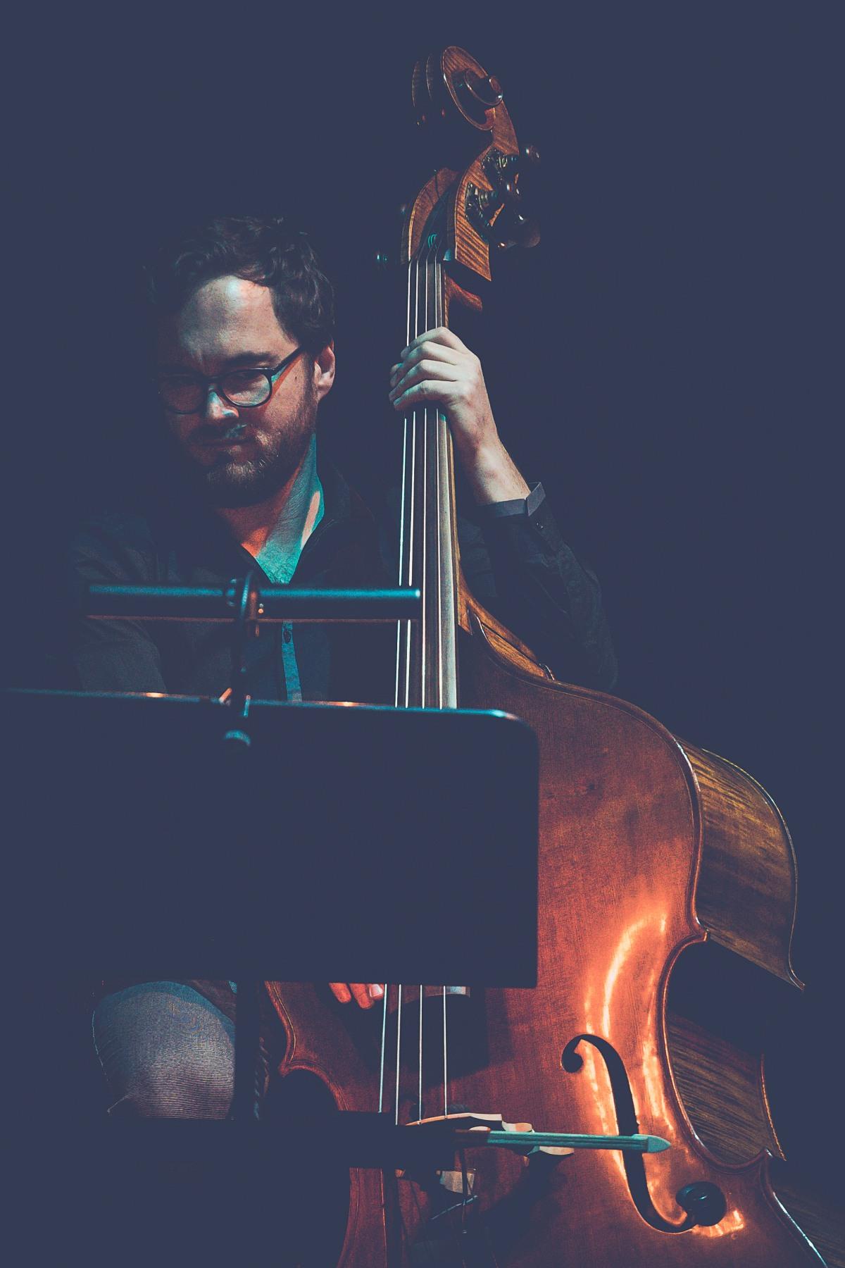 Jakub Olejnik gra na kontrabasie. Na pierwszym planie podświetlona partytura, na którą patrzy muzyk.
