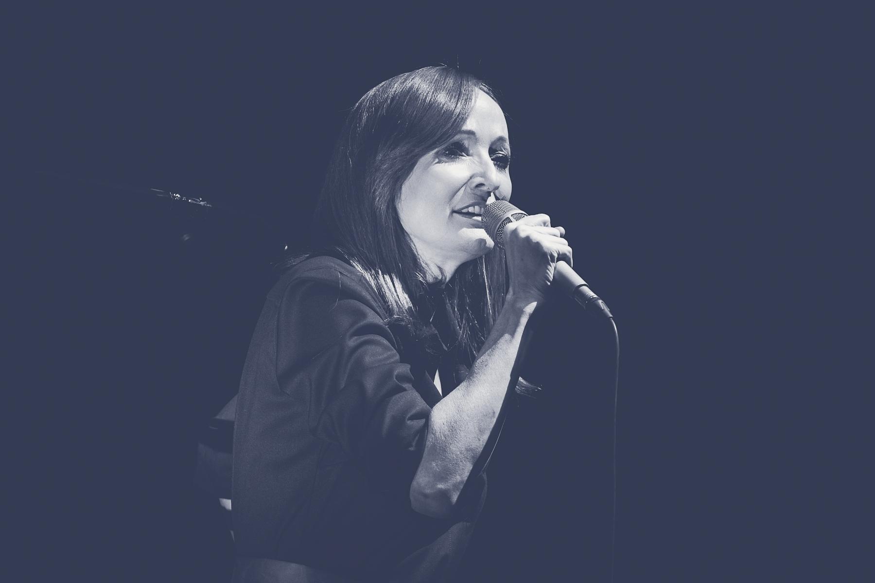 Monochromatyczne zdjęcie, na którym Justyna Szafran śpiewa do trzymanego w prawej ręce mikrofonu.