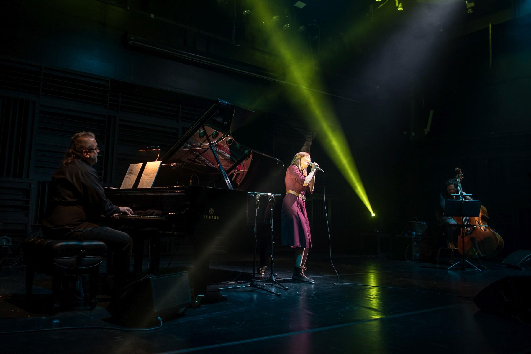 Justyna Szafran, ubrana w czerwoną sukienkę, stoi na scenie. Śpiewa, w obu rękach trzymając mikrofon. Po lewej Rafał Karasiewicz akompaniuje na fortepianie, po prawej Jakub Olejnik gra na kontrabasie. Scenę przecina zielone światło z reflektora.