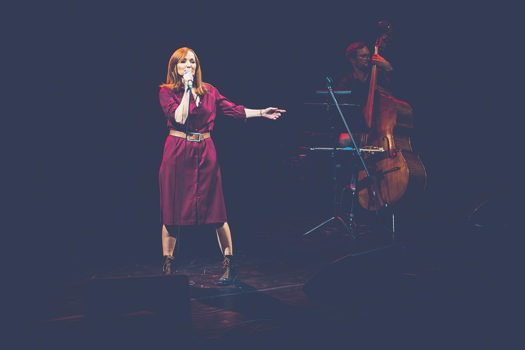 Po lewej stronie śpiewa Justyna Szafran. W prawej ręce trzyma mikrofon, lewą ma uniesioną na bok. Z prawej strony, w głębi sceny Jakub Olejnik gra na kontrabasie.