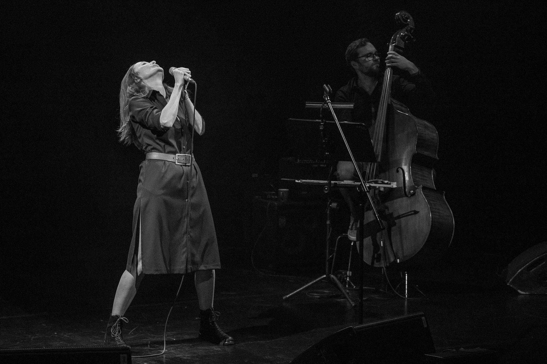 Monochromatyczne zdjęcie. Justyna Szafran trzyma oburącz mikrofon. Stoi w ekspresyjnej pozie z głową odchyloną do tyłu. W głębi sceny Jakub Olejnik gra na kontrabasie.