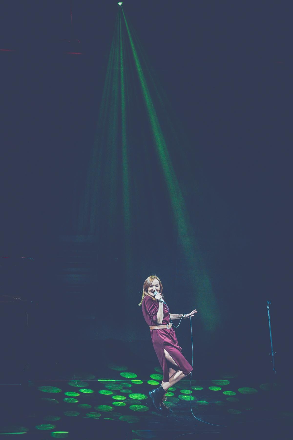 Justyna Szafran śpiewa. Dynamiczna, uchwycona w tańcu poza. Od góry oświetla ją snop zielonego światła z reflektora.