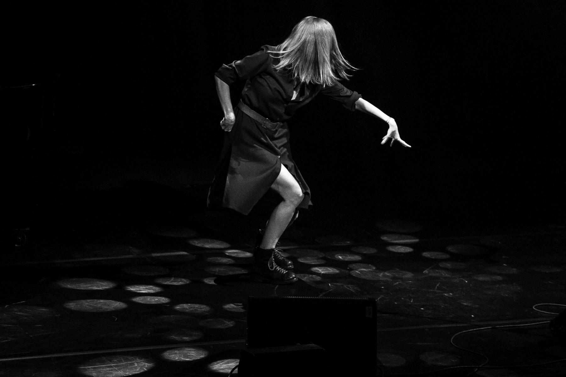 Na scenie Justyna Szafran w tanecznej, ekspresyjnej pozie, z twarzą zasłoniętą włosami. Zdjęcie monochromatyczne.