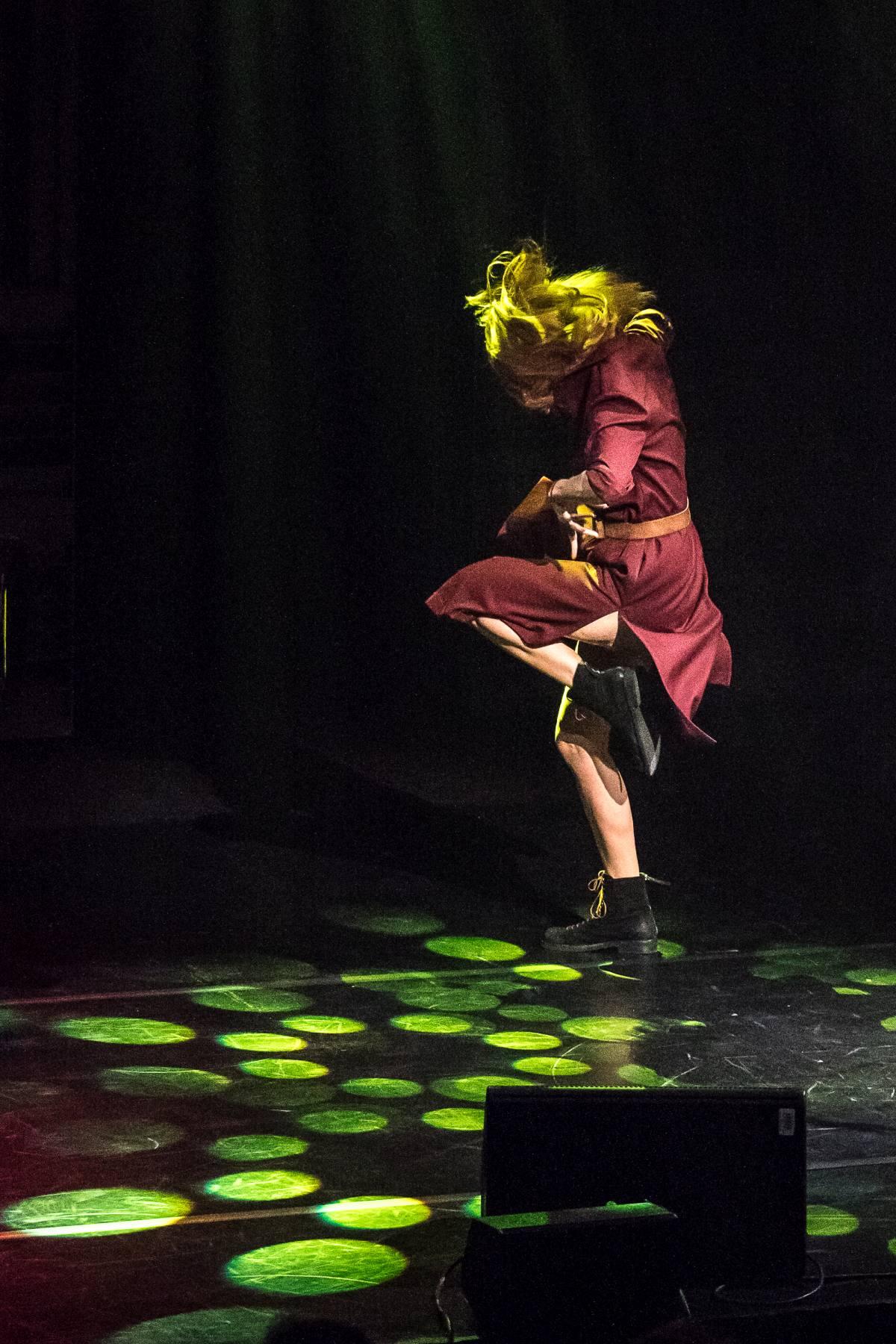 Justyna Szafran w dynamicznej, pełnej ekspresji tanecznej pozie. Stoi na jednej nodze, drugą, zgiętą w kolanie, unosi do góry. Włosy i suknia uchwycone w ruchu. Plamy zielonego światła na deskach sceny.