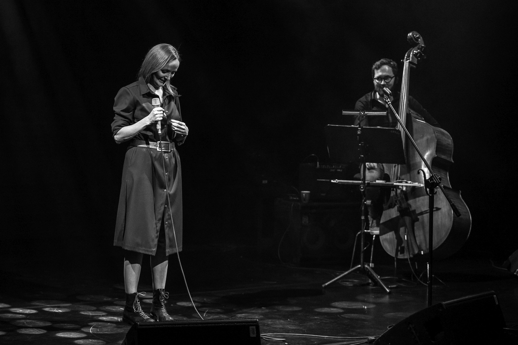 Po lewej stronie Justyna Szafran z mikrofonem z ręce i pochyloną głową. Po prawej Jakub Olejnik przy kontrabasie. Zdjęcie monochromatyczne.