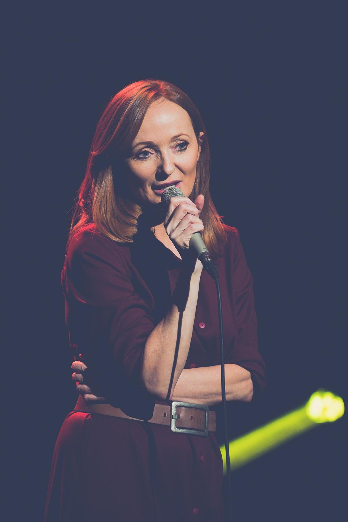 Bliski kadr obejmujący popiersie Justyny Szafran. Artystka śpiewa w jednej ręce trzymając mikrofon, a drugą trzymając założoną na pasie.