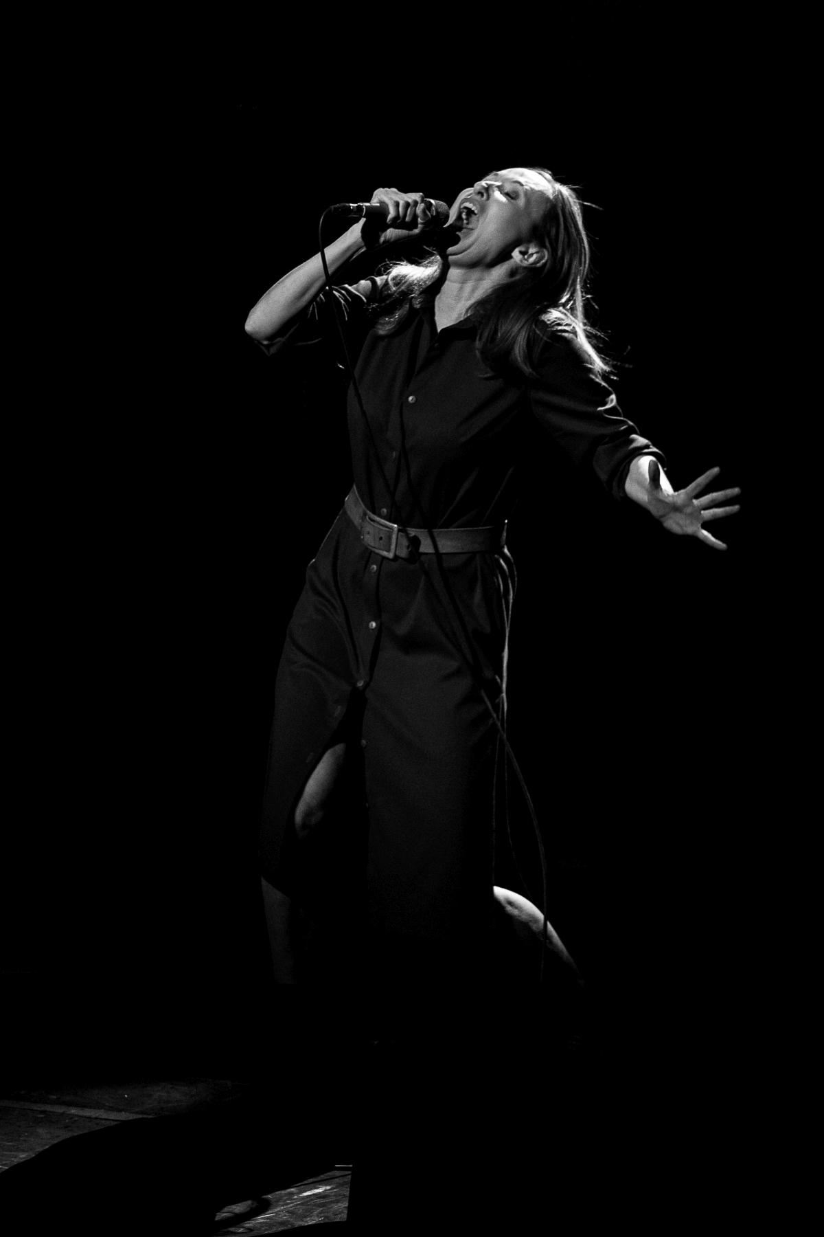 Śpiewająca Justyna Szafran. W jednej ręce trzyma mikrofon, drugą gestykuluje. Zamknięte oczy, wyrazista ekspresja twarzy, dynamiczna poza. Zdjęcie monochromatyczne.