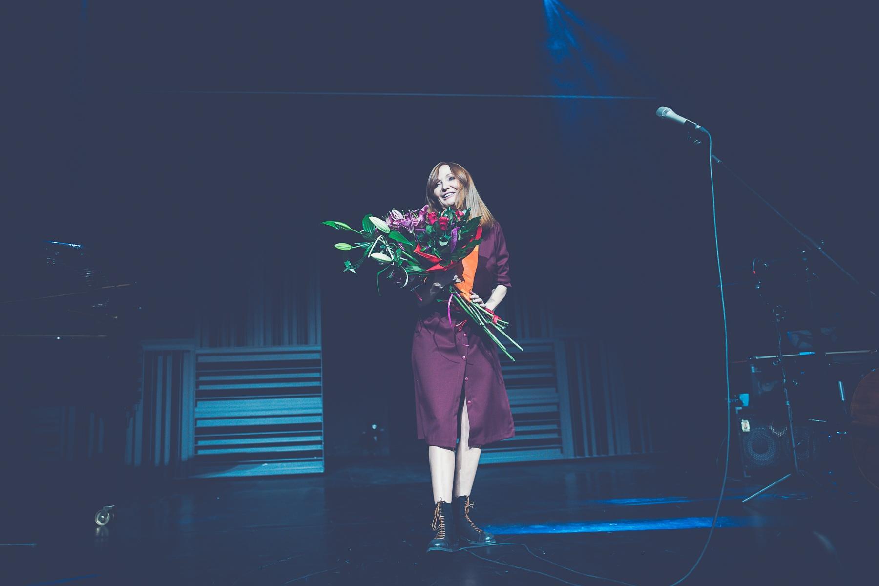 Justyna Szafran stoi uśmiechnięta na scenie, trzymając bukiet kwiatów – róż i lilii. Po prawej stronie mikrofon na statywie.