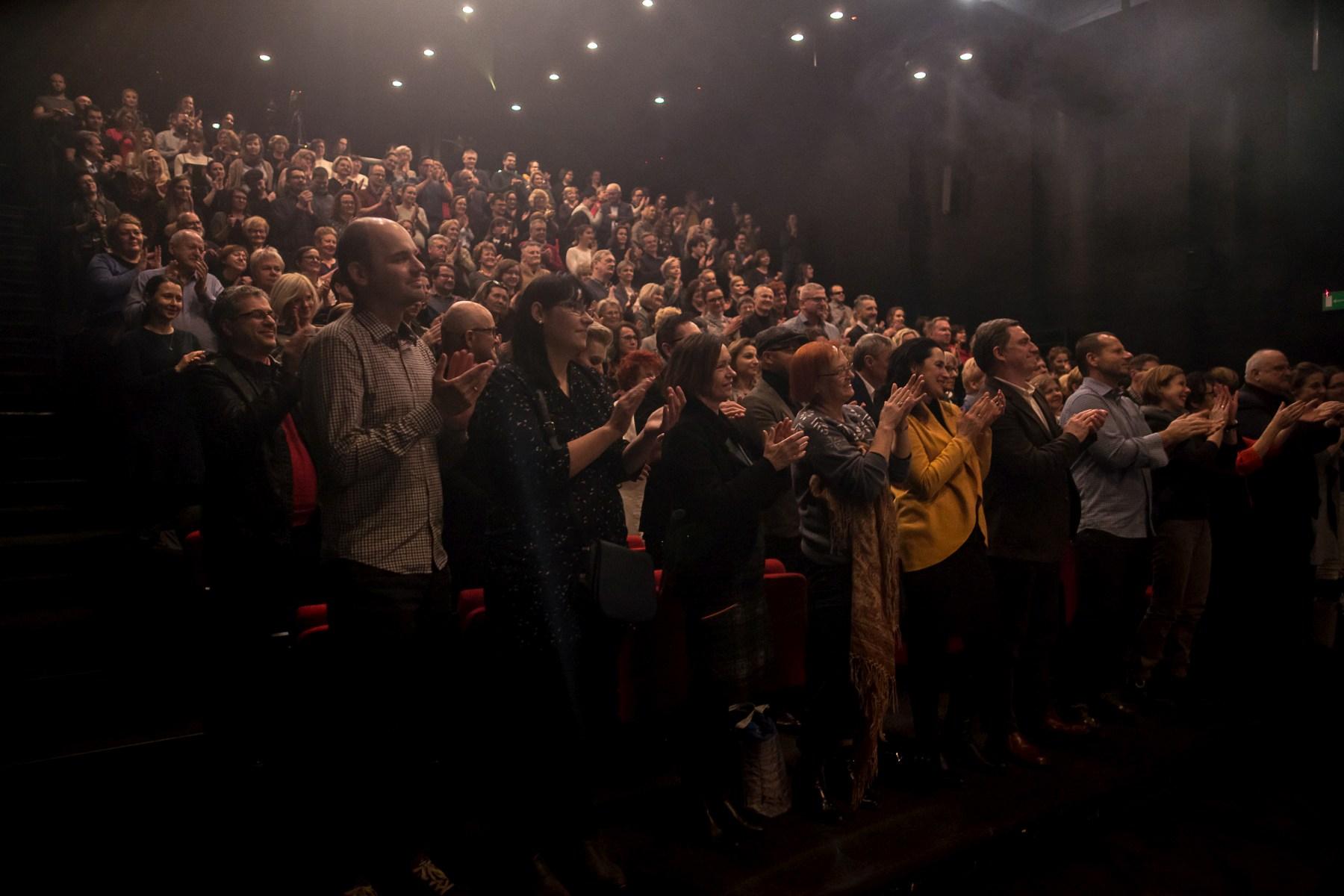 Ujęcie na zapełnioną widownię. Uśmiechnięci widzowie oklaskują artystów na stojąco.