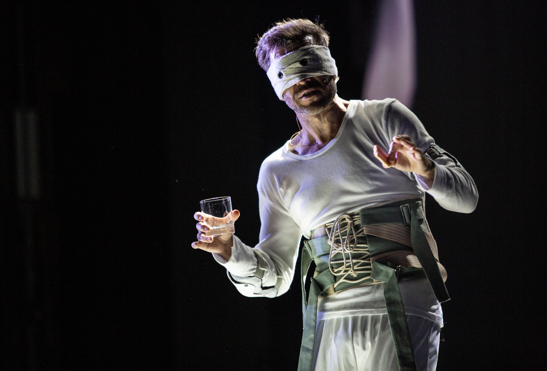Aktor w biały kostiumie sugerującym strój astronauty, z oczami przewiązanymi białą opaską-bandażem, trzyma w dłoni szklankę whisky. Stoi na czarnym tle