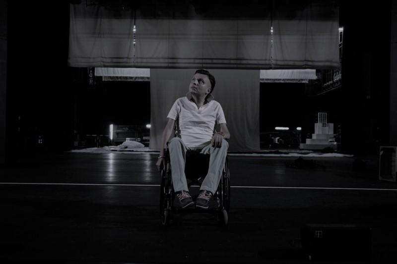 """Zdjęcie przedstawia Bartka na wózku, na środku Dużej Sceny Teatru Muzycznego Capitol. Patrzy w górę, nieco w prawo. Za nim widać dekoracje do """"Mistrza i Małgorzaty"""" w trakcie montażu."""