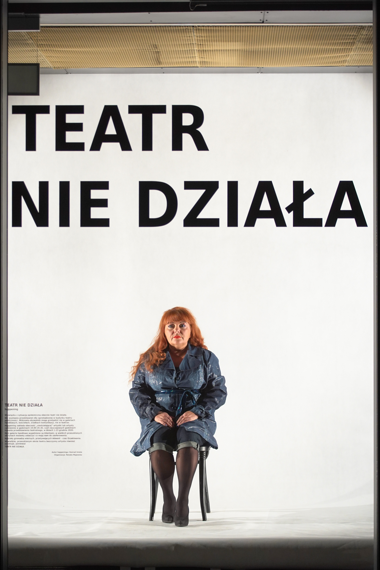 W witrynie teatru, na białym tle, na czarnym krześle siedzi aktorka. Na szybie widac duży czarny napis TEATR NIE DZIAŁA