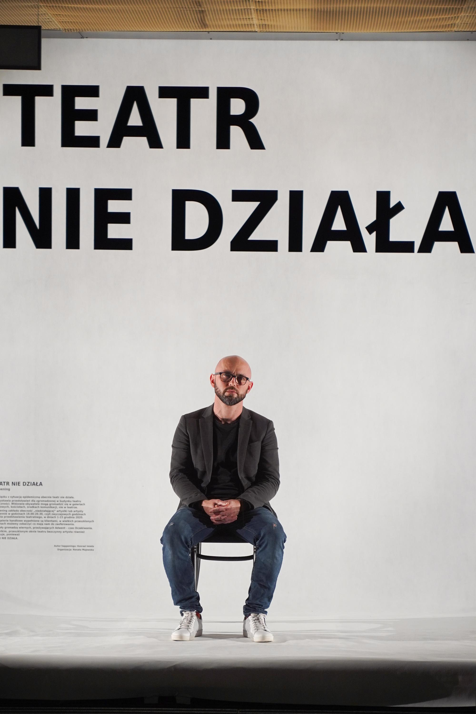 W witrynie teatru, na białym tle, na czarnym krześle siedzi aktor. Na szybie widac duży czarny napis TEATR NIE DZIAŁA