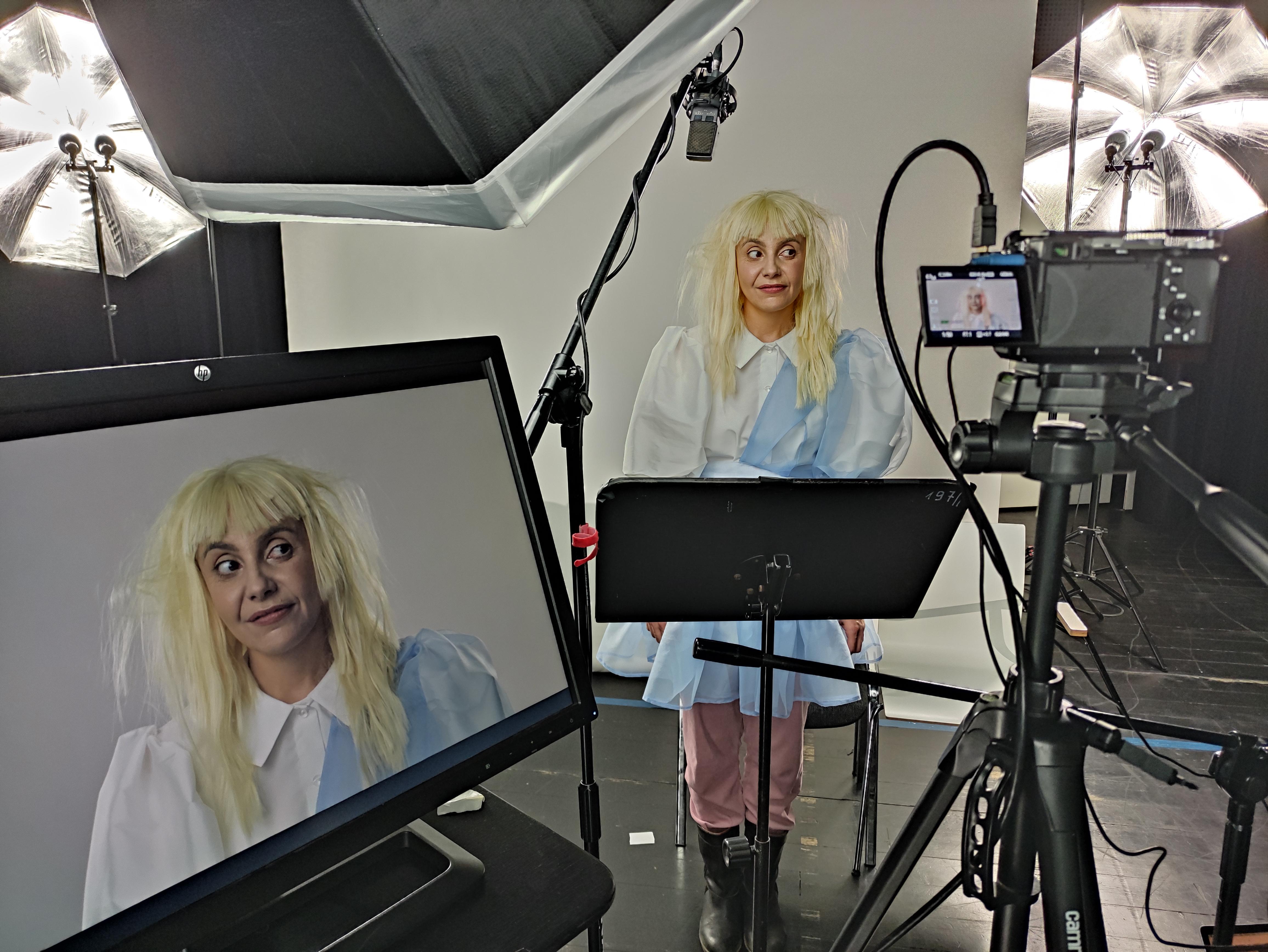 Na planie zdjęciowym. Aktorka grająca Alicję ma jasną, potarganą perukę i krótką niebieską sukienkę. Stoi przed mikrofonem i kamerą, jej twarz widać w poglądzie kamery na ekranie stojącego obok kamery monitora.