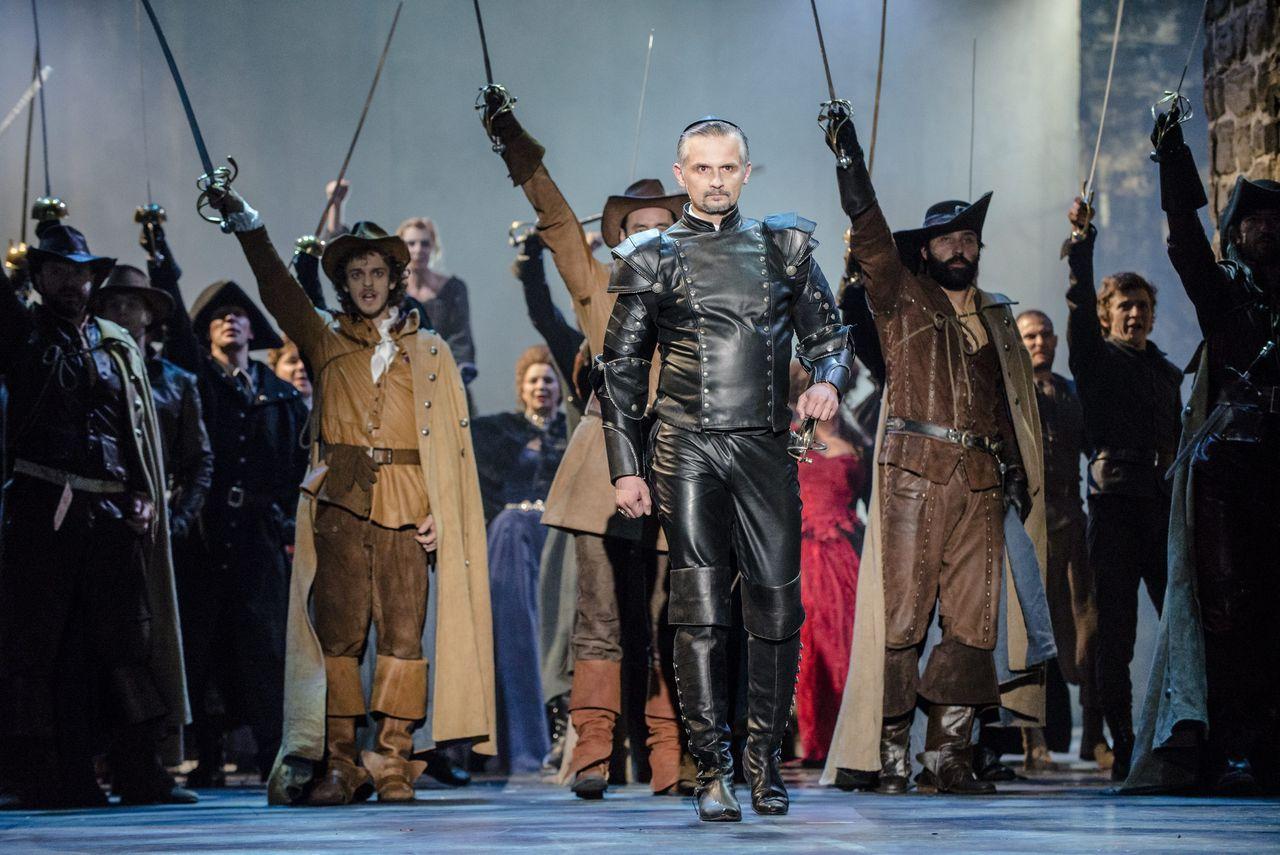 Mężczyzna w skórzanym mundurze idzie na czele wojska ze wzniesionymi rapierami, żołnierze ubrani są w XVII-wieczne mundury.